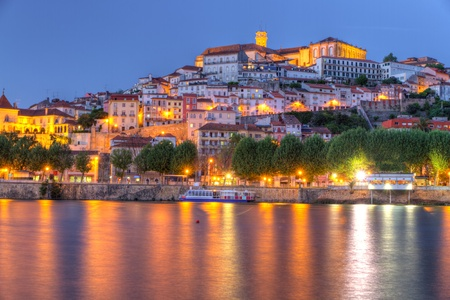 Old town of coimbra glows at night under a pretty summer sky, Portugal