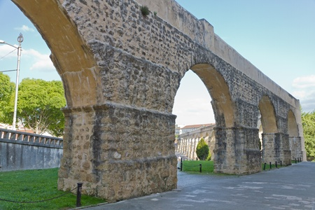 High arches of long aqueduct in Coimbra, Portugal photo