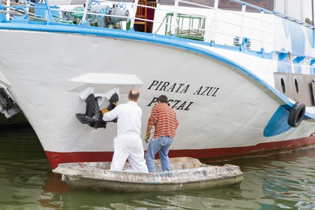 unorthodox: Porto - APRIL 20: Unidentified crew members do paint beauty repairs on a pleasure boat used to show tourists around river Duoro April 20, 2011 in Porto, Portugal. Tourism is big business in Oporto. Editorial