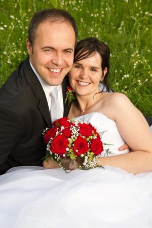 to wed: classica appena Mer coppia con abito scuro abito di nozze e bouquet nuziale rosso lo sposo tenendo la sua sposa su un prato