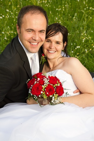 classical newly wed couple with wedding gown dark suit and red bridal bouquet the groom holding his bride on a meadow photo