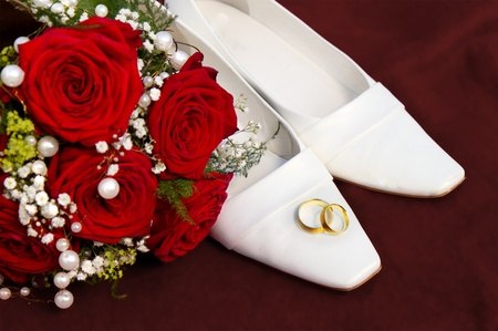 wedding symbol concept with white bridal dancing shoes a red roses bridal bouquet  and two entwined golden wedding rings on red velvet Stock Photo - 10324147
