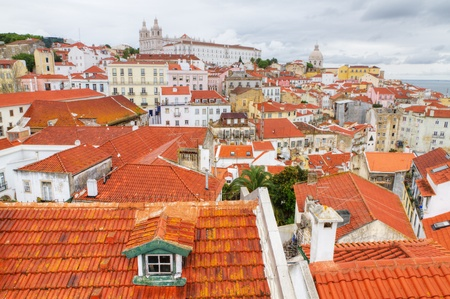 historic mediterranean architecture with small red roofs piled up houses and church in Lisboa, Portugal photo