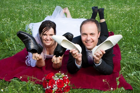 classical newly wed couple with wedding gown dark suit and red bridal bouquet the groom and  bride lie on a meadow having fun holding each others dancind shoes photo