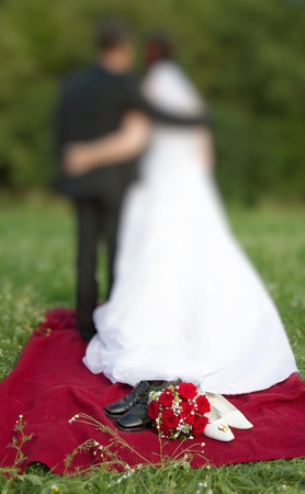 wedding symbol concept with white bridal dancing shoes a red roses bridal bouquet  and two entwined golden wedding rings newlyweds in the background photo