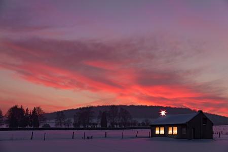 시골집: 눈 속에서 겨울 석양의 앞에 조명이 장식 된 창문이있는 작은 집 스톡 사진