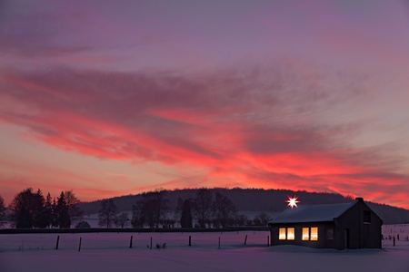 little house with decorated windows lighted in front of a winter sunset in snow