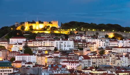 lisbon: historic mediterranean architecture with with castle  Sao Jorge and church at night with light in Lisboa, Portugal