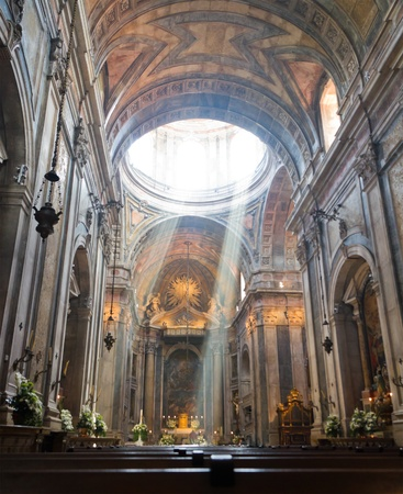 interior of church in, Lisbon, Portugal with wooden church benches and light beam of god going down from the cupola