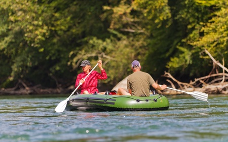 rafting: middle aged couple sits in rubber dinghy paddle in hand rowing together on a river in pretty natural summer settings
