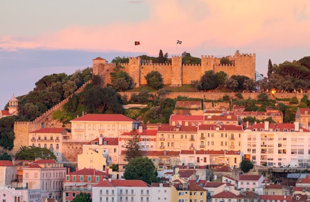lisboa: historic mediterranean architecture with with castle  Sao Jorge at sunset in Lisboa, Portugal