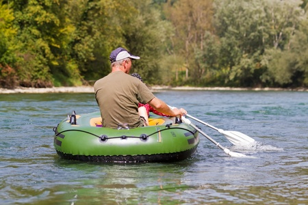 middle aged couple sits in rubber dinghy paddle in hand rowning together on a river in pretty natural summer settings photo