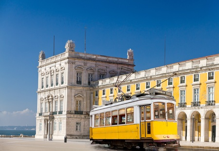 historic classic yellow tram of Lisbon built partially of wood in front of Lisbons central square Praca de Comercio, Portugal