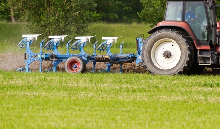 ploughing: tractor with plough ploughing a grass covered field, concept for agriculture business
