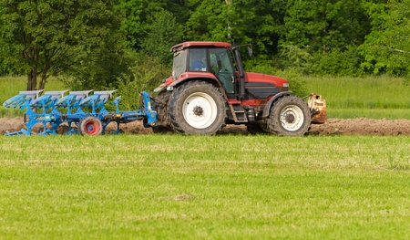 tractor with plough ploughing a grass covered field, concept for agriculture business  photo