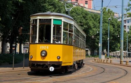 railway history: historic classic yellow tram of Milan on winding rails, Italy