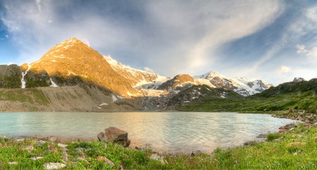 Swiss alpine mountain lake with  meadow, a glacier and near Susten pass in summer at sunset, Switzerland photo
