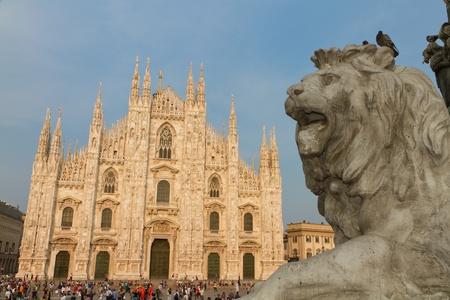 Statua del leone in Piazza del Duomo con la cattedrale al tramonto Milano, Italia