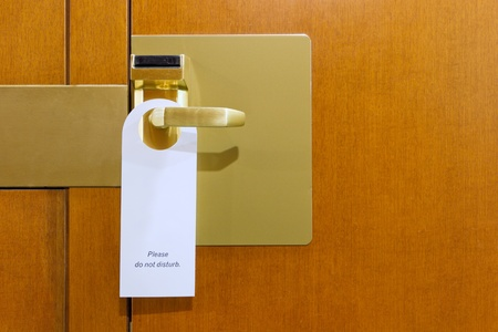 room for text: classic do not disturb sign on brass and wood hotel room door cleaned with copyspace for your text
