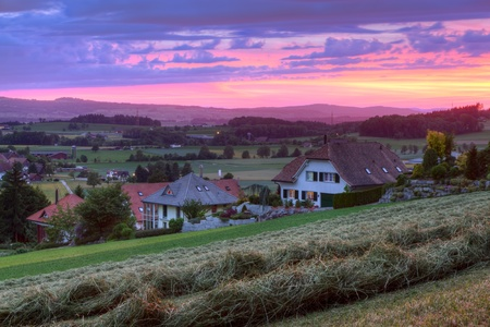 sunset over village houses surrounded by fields and hay, a summer day in Affoltern Switzerland photo