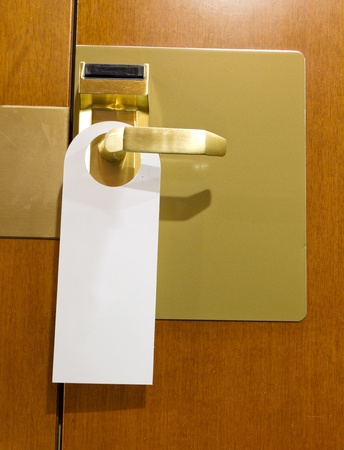 cleaned: classic do not disturb sign on brass and wood hotel room door cleaned with copyspace for your text