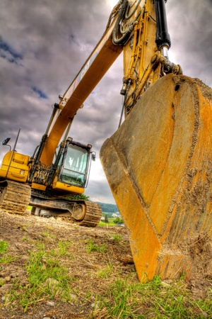 digger: digger showing menacing strength, power, size, weight of this road construction vehicle