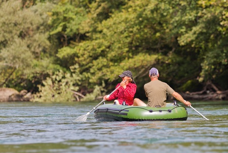 mid life: middle aged couple sits in rubber dinghy paddle in hand rowing together on a river in pretty natural summer settings