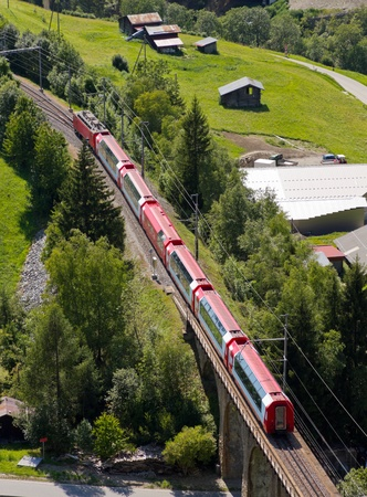 express: aerial view on glacier express panorama train crossing bridge and green rural valley, Vallais, Switzerland Stock Photo