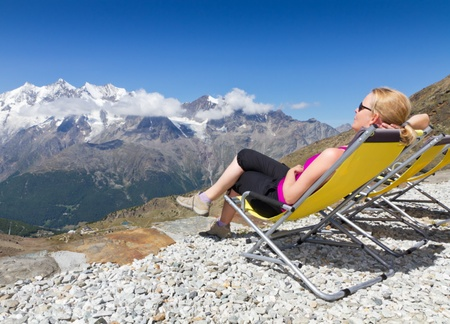 honorarios: mujer joven disfruta del sol y se relaja en una silla de lona alpino rodeado de monta�as cubiertas de nieve en Saas Fee, Suiza
