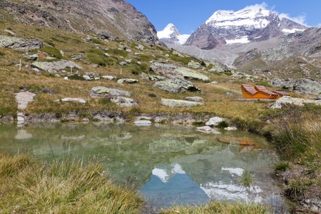 saas fee: high alpine lake with mountains reflecting in it and relax chairs in summer, Saas Fee, Switzerland Stock Photo