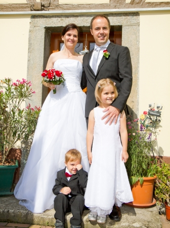 newly wed couple and children with wedding gown, dark suit and rose bridal bouquet: stand in front of there home happy