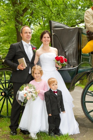 newly wed couple and children with wedding gown, dark suit and rose bridal bouquet: in front of horse carriage photo