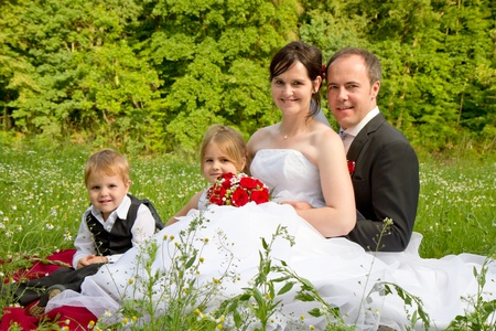 newly wed couple and children with wedding gown, dark suit and rose bridal bouquet: sit on meadow proud and happy photo