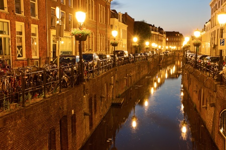 along: Canal in Utrecht, Netherlands. Houses, bicycles  and vintage street lamps along the canal at sunset.