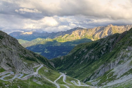 bridging: Old road with tight serpentines on the southern side of the St. Gotthard pass bridging swiss alps at sunset in Switzerland, europe