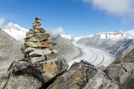 concept for hiking, climbing, walking and outdoor adventures:  mountain top with rock cairn marking above Aletsch glacier Switzerland 版權商用圖片