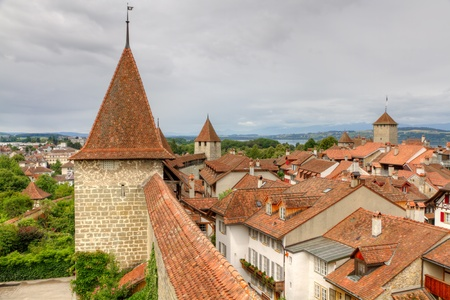 swiss culture: Murten old town with narrow lanes city wall, watch tower  and clay shingle roofs, Switzerland