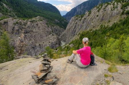 valley below: young fit woman enjoys view over Aletsch valley with Belalp Riederalp Gruensee suspension bridge down below, Switzerland Stock Photo