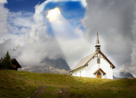 concept for christianity, god, belief, relief and trust: white plain mountain chapel at Belalp near Aletsch glacier in a ray of light, Valais, Switzerland Stock Photo - 12875566
