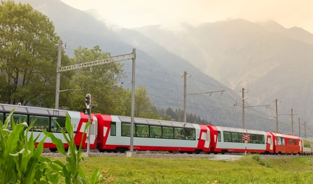 Glacier express train passes high mountain valley, Switzerland