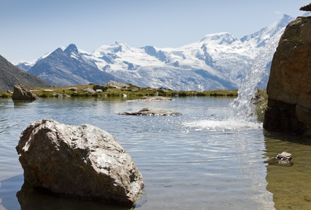 saas fee: high alpine lake with litlle waterfall in summer, Saas Fee, Switzerland