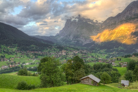 eiger: Famous alpine town Grindelwald in valley at sunset in front of mountain Eiger north face, Switzerland