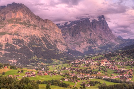 Famous alpine town Grindelwald in valley at sunset in front of mountain Eiger north face, Switzerland photo