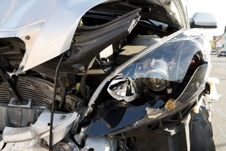 totaled: frontal car crash wreck with broken headlight details