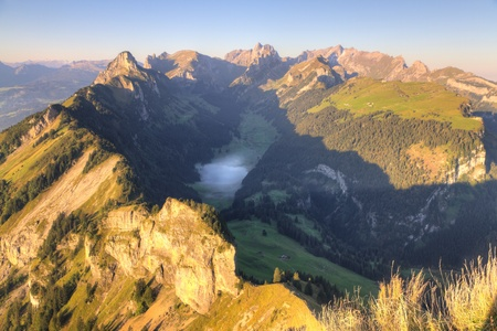 deep green valley with lake and mist floating on it and houses surounded by high,steep, rocky mountain walls at Säntis, Switzerland