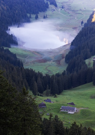 deep green valley with lake and mist floating on it and mountain peaks reflecting surounded by high,steep, rocky mountain walls at Säntis, Switzerland Stock Photo - 13328228