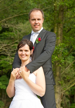 newly wed couple with wedding gown, dark suit and rose bridal bouquet: groom and bride hand in hand proud and happy photo