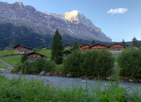 river and timber chalet huts with dewy meadow and mountain Eiger top glowing in early morning light, Grindelwald, Switzerland photo