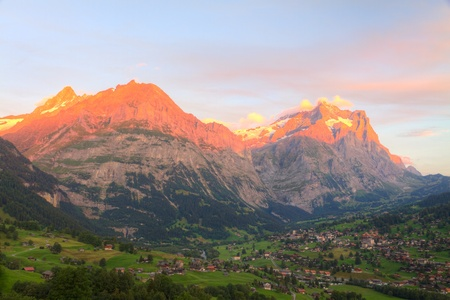 Alpenglow over alpine town Grindelwald in valley at sunset in front on mountain Eiger north face, Switzerland photo