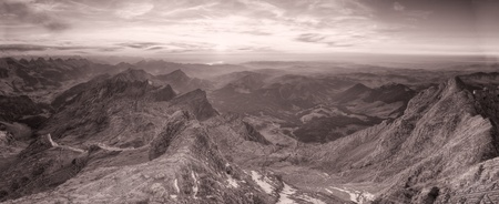 strange mountain: black and white panorama of high alpine ragged sharp karst mountain top ranges disapear in misty distance at sunset, Switzerland  Stock Photo